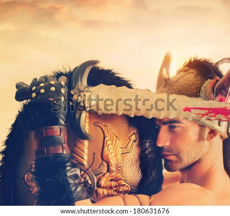 Powerful ancient warrior with bloody sword and helmet beneath a dramatic sky and overall vintage toning for antique effect - stock photo
