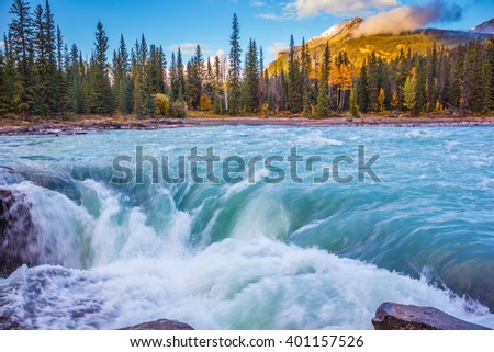 Powerful and scenic Athabasca Falls. Emerald water roars and foams on steep slope. Canada, Jasper National Park - stock photo