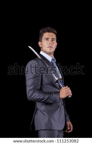Powerful businessman holding a ninja sword (isolated on black) - stock photo