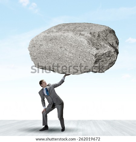 Powerful businessman holding huge stone above head - stock photo