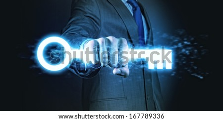 Powerful businessman holding key in his fist - stock photo