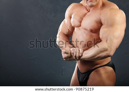 Powerful chest and hand muscles of undressed tanned wet bodybuilder - stock photo