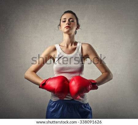 Powerful girl wearing red boxing gloves