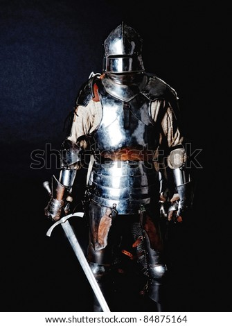 Powerful heavy fighter with sword and helmet. Isolated on black background. - stock photo