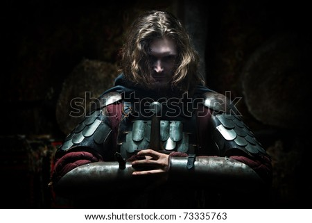 Powerful knight in the armor with the sword. Dark background. - stock photo