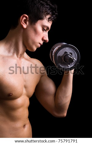 Powerful muscular young man lifting weights - stock photo