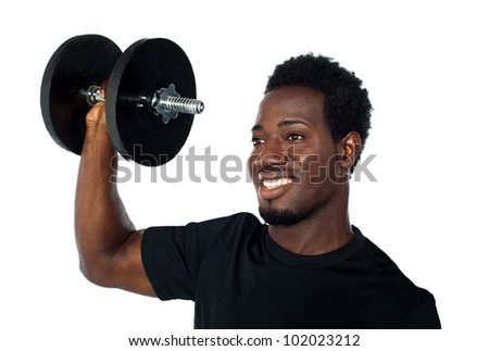 Powerful muscular young man lifting weights. Smiling and looking away