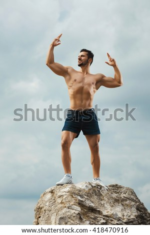 Powerful. Portrait of a handsome muscular man posing on nature landscape standing on a stone.