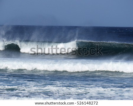 Powerful waves breaking on a sandy shore under a blue sky 5481