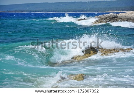 Powerful waves crushing on a rocky coastline in Croatia - stock photo