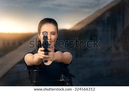 Powerful Woman Aiming Gun Action Movie Style - Portrait of a girl in a heroine cosplay  costume pointing gun at the camera   - stock photo