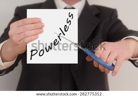 Powerless, man in suit cutting text on paper with scissors
