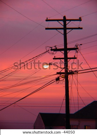 Powerline backed by sunset - stock photo