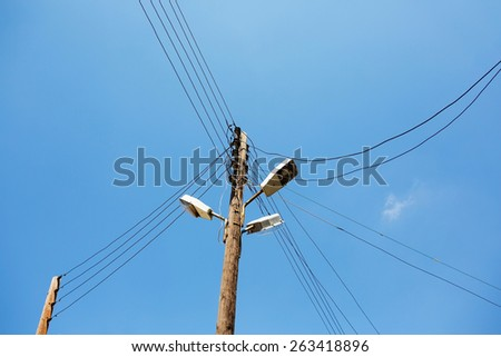 Powerline on wooden pillar. Electricity poles with a lamp and wires. - stock photo