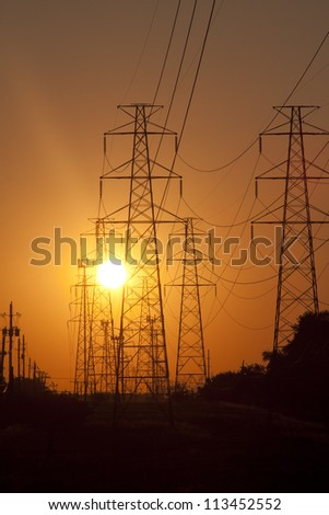 Powerlines disappearing into the sunset - stock photo