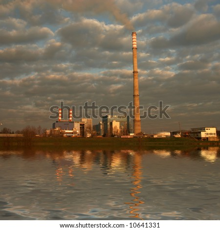 Powerplant with cloudy sky and reflection in river - stock photo