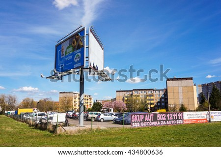 POZNAN, POLAND - APRIL 12, 2015: Parked cars on a secured parking lot with advertisement billboard