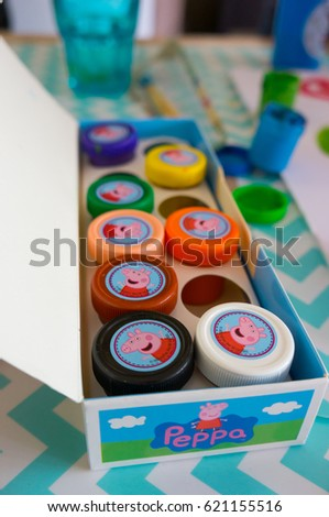 POZNAN, POLAND - APRIL 14, 2017: Peppa Pig water color set in different colors in small containers in open box on table in soft focus