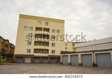 POZNAN, POLAND - APRIL 07, 2016: Row of garages with a apartment block at the end on a cloudy day - stock photo