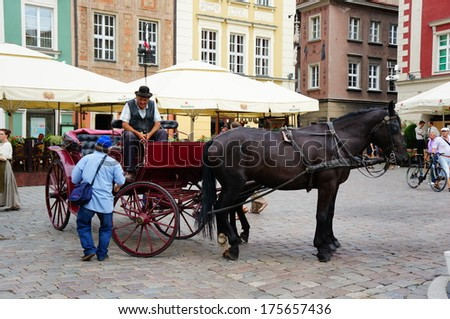 POZNAN, POLAND - AUGUST 18, 2013: Man having a conversation with a horse carriage rider in the old square