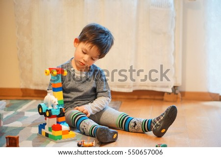 POZNAN, POLAND - JANUARY 07, 2017: Unidentified two years old boy playing with Lego Duplo toy blocks on a floor in a room