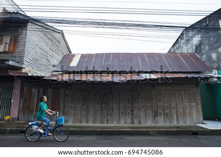 PRACHUAP KHIRI KHAN, THAILAND - July 31, 2013 : Woman is riding a bicycle on a street in the old town at Prachuap khiri khan ,Thailand
