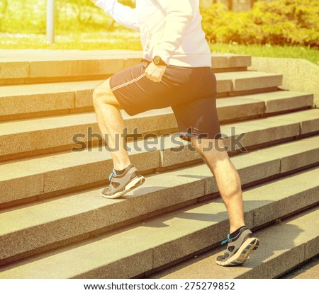 Practice - Close up of young man running up the stairs - stock photo