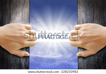 Practice word floating and shining in the sky while two hands opening an old wooden door. - stock photo