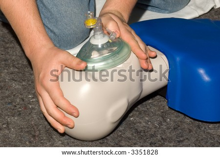 Practicing CPR Mask on a manikin. - stock photo