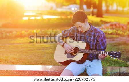 Practicing in playing guitar. Handsome young man playing on acoustic guitar - stock photo