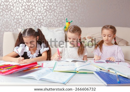 Practicing writing. Group of cute little school girls writing with colorful pens and pencils in their note pads  - stock photo