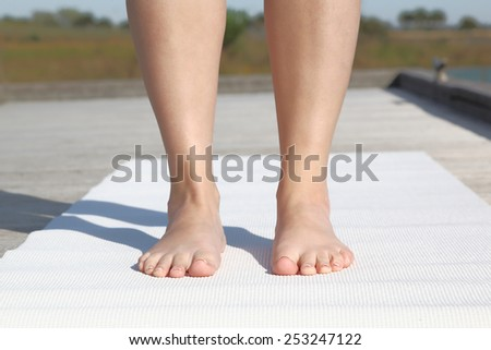 Practicing yoga. Woman standing outside on yoga mat. closeup - stock photo