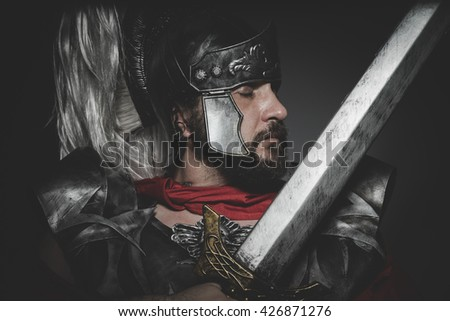 Praetorian Roman legionary and red cloak, armor and sword in war attitude - stock photo