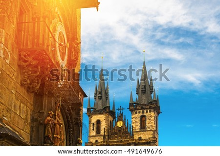 Prague astronomical clock and Tyn Church of Our Lady  against blue sky