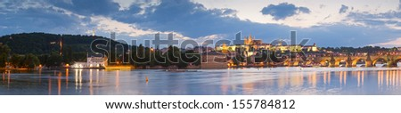 Prague Castle, Charles Bridge and St Vitus Cathedral reflected in the Vltava river running through the heart of the city of Prague in the Czech Republic. - stock photo