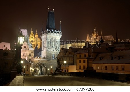 Prague Castle from Charles bridge at night with tower and St. Nicholas church - stock photo