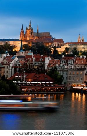 Prague Castle with surrounding buildings across Vltava river in the evening - stock photo