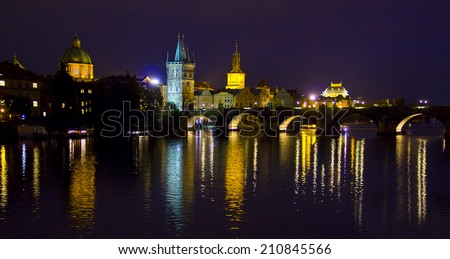 Prague Charles bridge at night with reflections in the river - stock photo