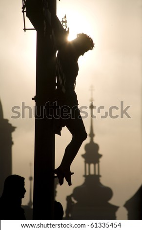 Prague - cross from H. Hilger 1629 on the charles bridge by sunrise - silhouette - stock photo