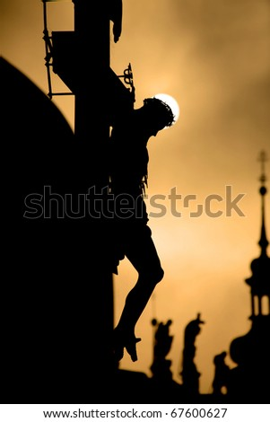 Prague cross on the charles bridge by sunrise - silhouette