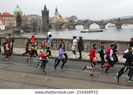 PRAGUE, CZECH REPUBLIC - APRIL 6, 2013: Athletes run over the Manes Bridge on the Vltava River during the Prague international marathon in Prague, Czech Republic.  - stock photo