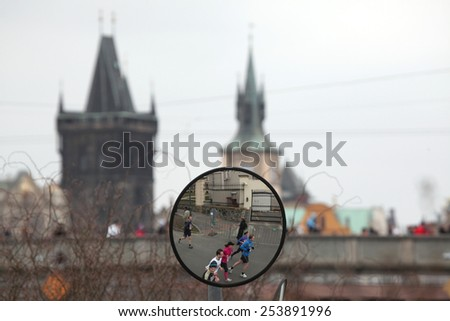 PRAGUE, CZECH REPUBLIC - APRIL 6, 2013: Convex mirror with the reflection of athletes running the Prague international marathon in Prague, Czech Republic. The Charles Bridge is seen in the background. - stock photo