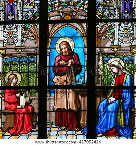 PRAGUE, CZECH REPUBLIC - APRIL 2, 2016: Stained Glass window in St. Vitus Cathedral, Prague, depicting Jesus as an adolescent studying the holy texts, in the company of Saint Joseph and Mother Mary - stock photo