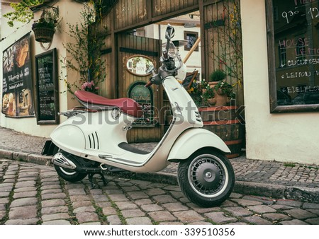 Prague, Czech Republic - April 27, 2015: Vespa parked near cafe in Prague, Czech Republic - stock photo