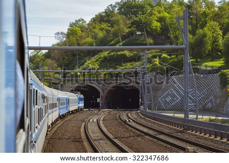 PRAGUE, CZECH REPUBLIC - AUGUST 26, 2015: Passenger train departs from the main train station of Prague to Kutna Hora. The locomotive enters the tunnel. Prague, Czech Republic - stock photo