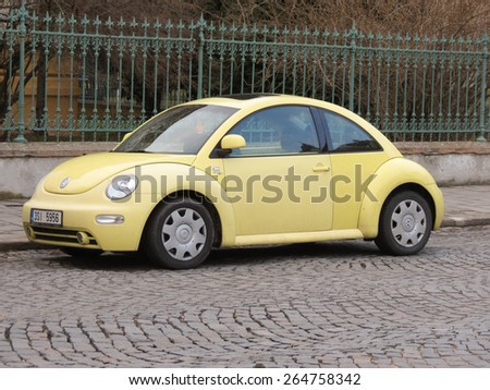 PRAGUE, CZECH REPUBLIC - CIRCA MARCH 2015: Yellow Volkswagen New Beetle car parked in a street of the city centre.  - stock photo