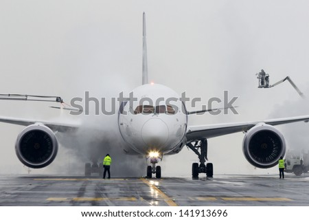 PRAGUE, CZECH REPUBLIC - DECEMBER 16: De-icing LOT Polish Airlines, Boeing B787 Dreamliner at Prague Airport on December 16, 2012. Polish Airlines, is the flag carrier of Poland. Based in Warsaw. - stock photo