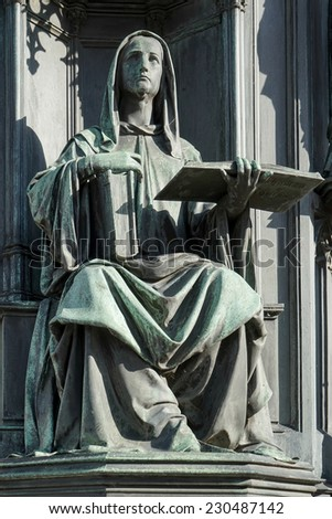 PRAGUE, CZECH REPUBLIC/EUROPE - SEPTEMBER 24 :A statue of a woman holding the books of Thomas Aquinas at the base of Statue of King Charles IV on Charles Bridge  in Prague on September 24, 2014 - stock photo