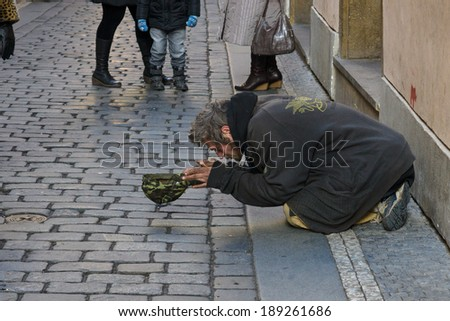 PRAGUE, CZECH REPUBLIC - FEBRUARY 03, 2014: Beggar kneeling begging in the Old Town.