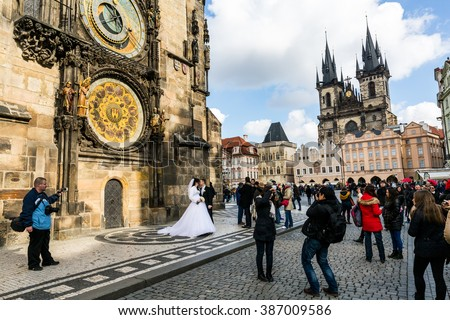 PRAGUE, CZECH REPUBLIC - FEBRUARY 26: View of a wedding photoshooting in front of the astronomical clock in Prague on February 26, 2016. Prague is the capitol city of Czech Republic. - stock photo